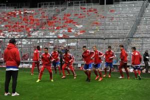 Nicht alltäglich: Die Spieler von buntkicktgut wärmen sich vor der Südkurve in der Allianz Arena auf